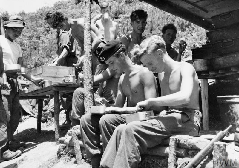 Private Ken Meade (left) and Private Eric Collier from the 1st Battalion, The King's Shropshire Light Infantry eat a meal at one of the unit's posts in Korea.