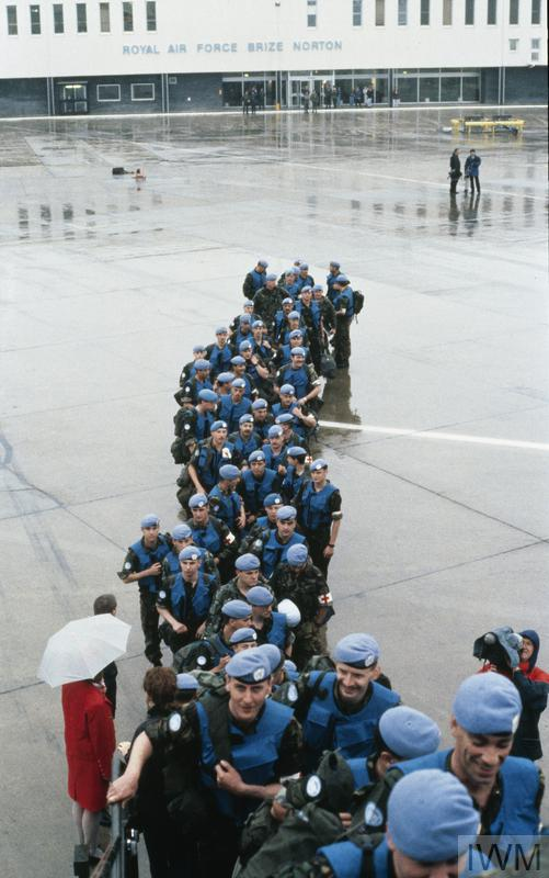 British troops wearing blue United Nations berets, insignia and identification vests prepare to board a troop transport aircraft at RAF Brize Norton for Bosnia in early 1993. In the background, a television cameraman films the event.
