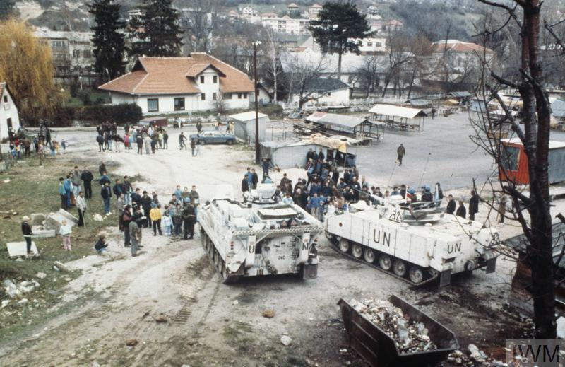 View of the market place at Travnik, Bosnia shortly after the arrival of British forces in Bosnia at the start of Operation GRAPPLE. Civilians cluster around two Warrior armoured fighting vehicles of 1 Cheshire Regiment.