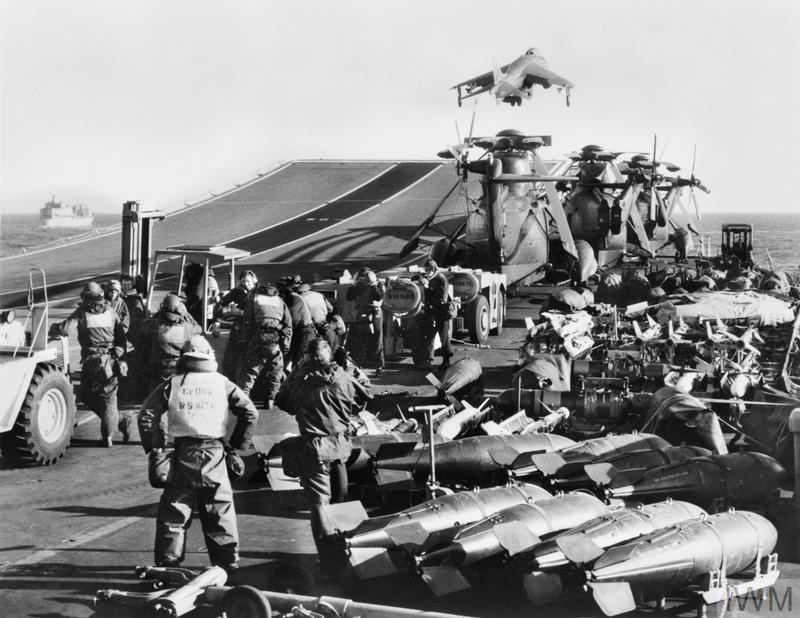 Flight deck operations on board HMS HERMES. A Sea Harrier takes off from the ski-jump while various missiles, helicopters and vehicles crowd the flight deck of the carrier. The arms front to back include: 1000lb GP bombs with type 114 'Slick' tails, 1000lb GP Bombs with Type 117 parachute 'retarded' tails, Sidewinder air-to-air missiles and Sea Skua air-to-surface missiles.