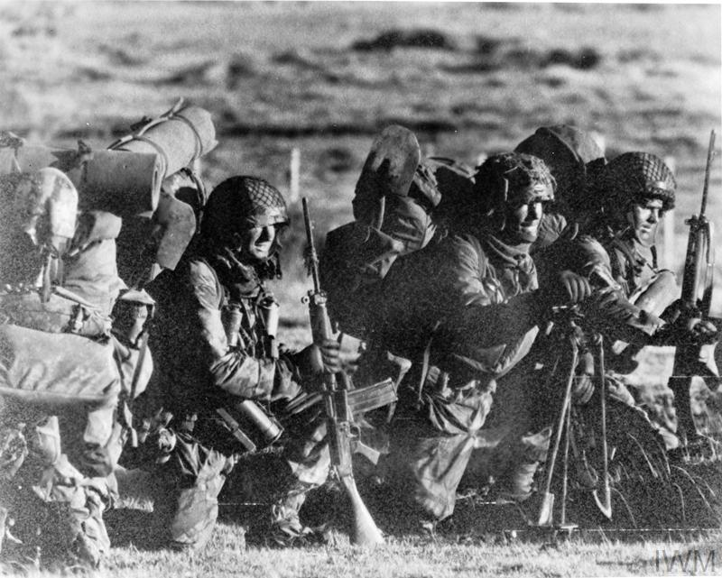 Heavily laden British soldiers of 11 Platoon, D Company, 2 Para wait to embark in a helicopter at Fitzroy during the Falklands Conflict. The three seen are (left to right) Private Dave Parr (who was killed shortly afterwards during the assault on Wireless Ridge - having earlier been shot at Goose Green), Lance Corporal Neil Turner and Private Terry Stears.