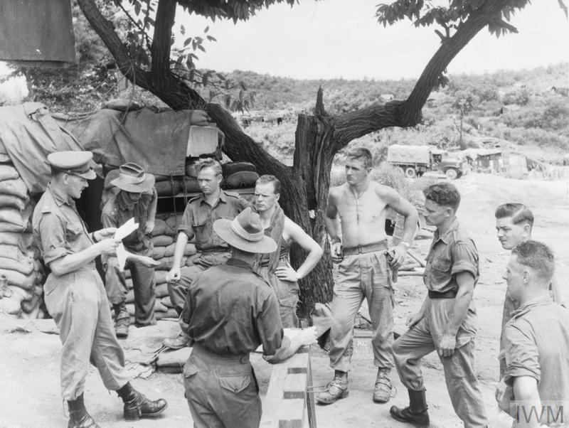 Major T H Wilson of the 2nd Battalion Royal Australian Regiment reads ceasefire instructions to Headquarters personnel near the Battalion Command Post in Korea on 27 July 1953.