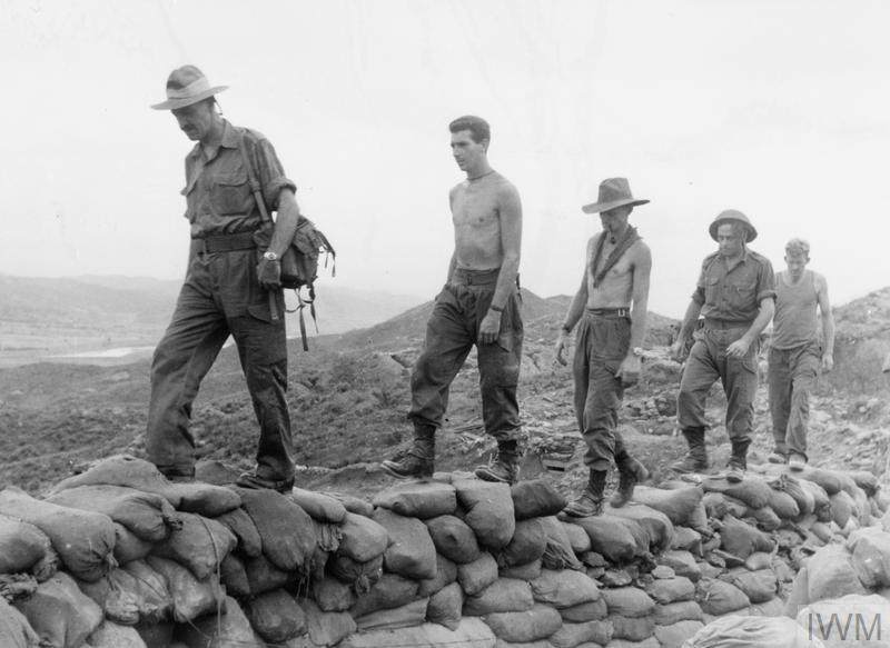 "Soldiers of the 2nd Battalion Royal Australian Regiment walk along the top of their sandbagged trenches on ""The Hook,"" the morning after the Cease Fire."
