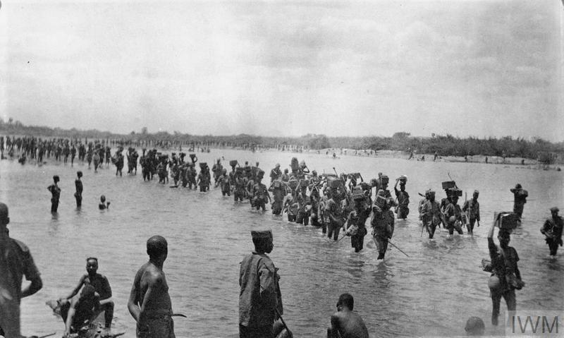 First line small ammunition column of the 2nd/4th Battalion, King's African Rifles crossing the Lurio River during operations in Portuguese East Africa.