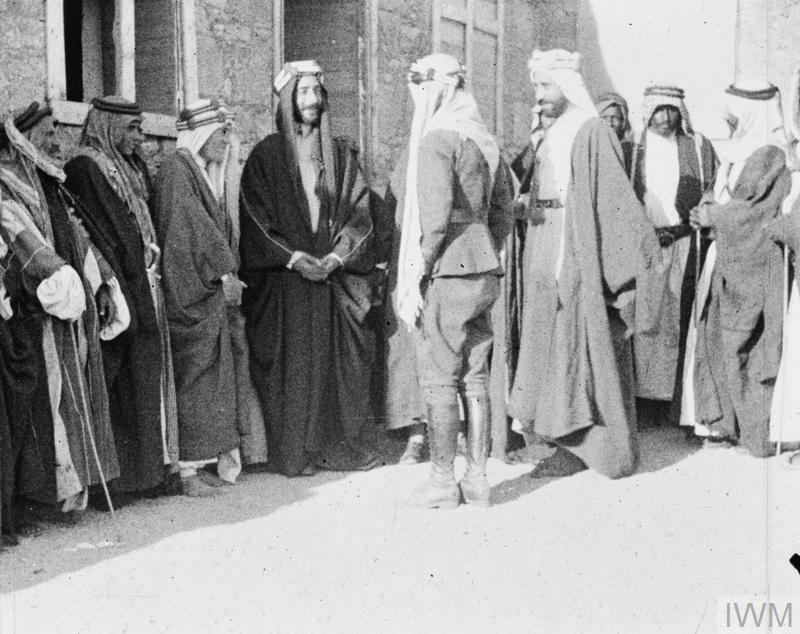 Colonel T.E. Lawrence with King Feisal. Chatting to Lowell Thomas.