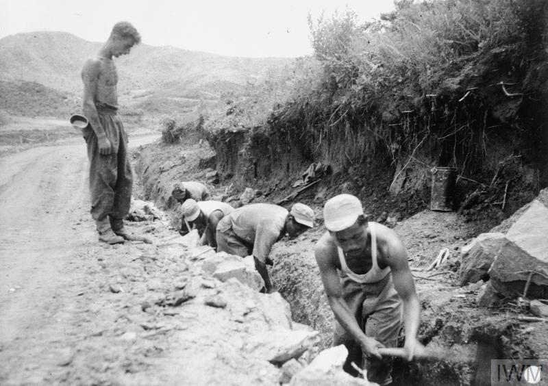 Four men of the Korean Service Corps redigging a monsoon drainage ditch alongside a road leading to The Hook. The men are supervised by Sapper Edwin Darwood, a member of 28 Field Engineer Regiment, Royal Engineers.