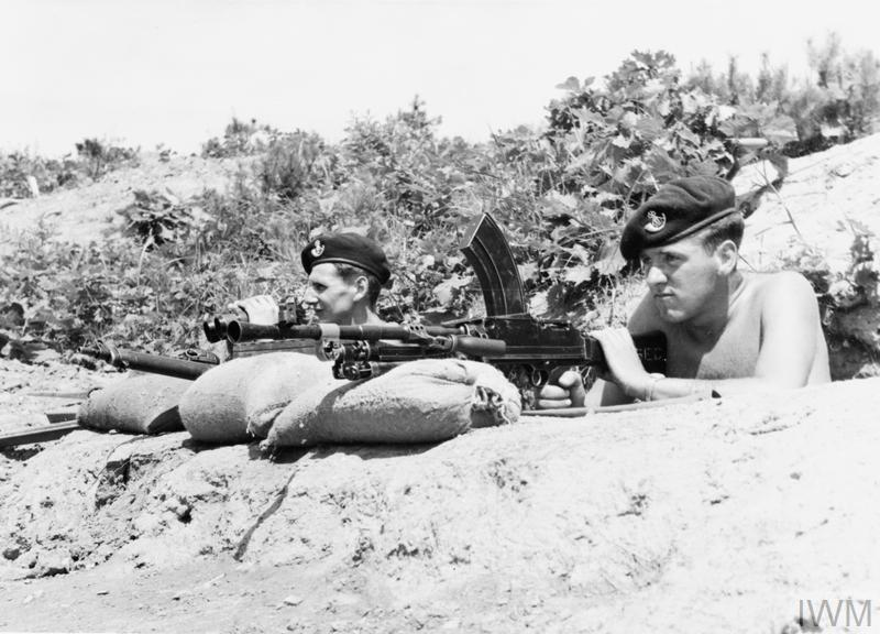 Lance Corporal Les Markwick (with binoculars) and Private Sten Munns, both with the 1st Battalion, The King's Shropshire Light Infantry, prepare to fire on Chinese positions witha Bren gun.