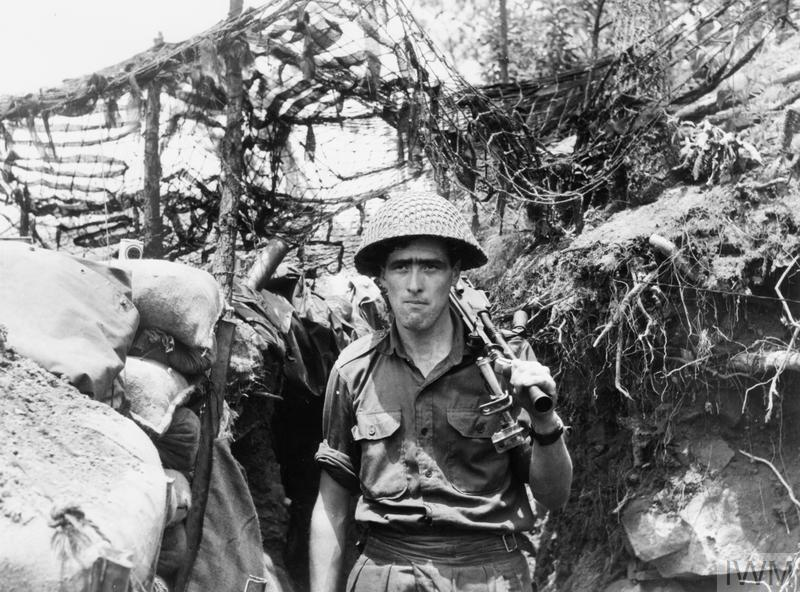 Walking along a typical hillside trench is Private Jack Crawford of Company A, 3rd Battalion, Royal Australian Regiment.