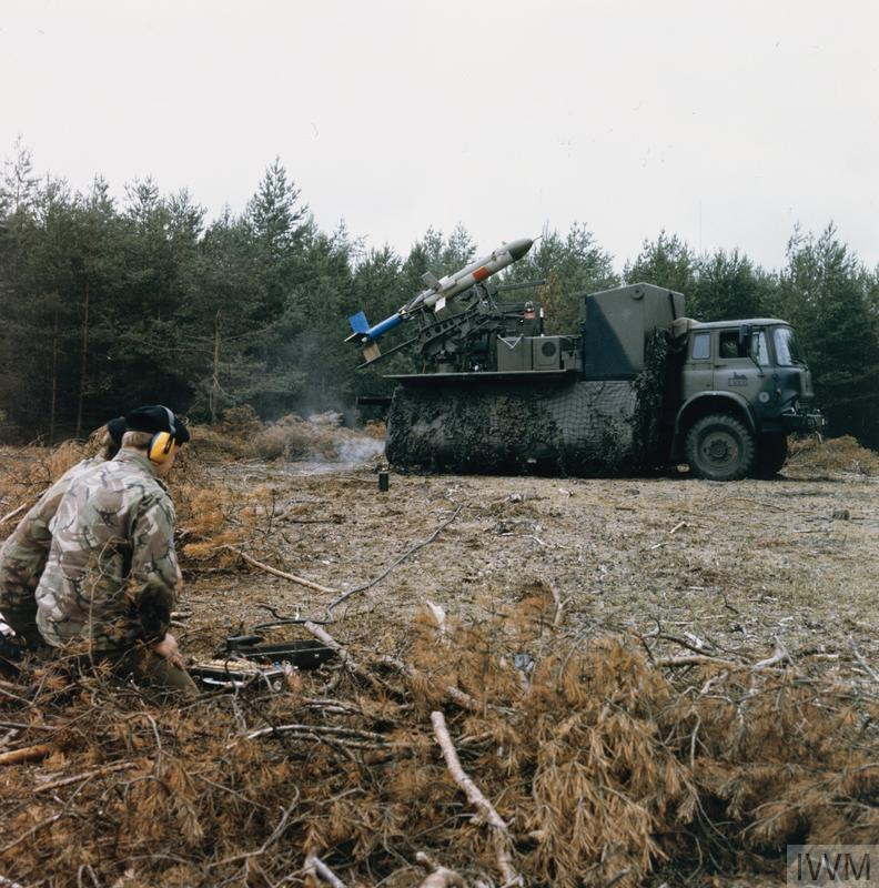 Two soldiers prepare to launch an RPV ( Remotely Piloted Vehicle ) drone from a Bedford three ton truck on exercise in Germany, probably in the early 1980s. The men, kneeling several yards away from the vehicle, control the drone through a remote keypad and joystick.