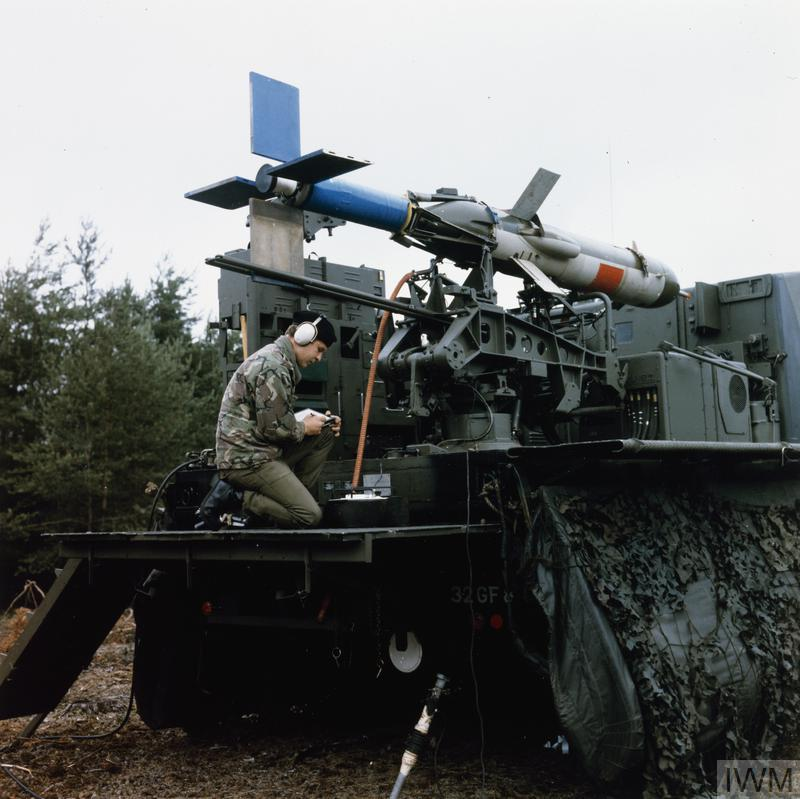 A technician serving with a Royal Artillery divisional locating battery checks the launch mechanism of a British Army Canadair RPV (Remotely Piloted Vehicle) Midge Surveillance Drone on the back of a Bedford truck. The rocket powered Midge Drone was designed to carry out aerial photo reconnaissance on a pre-programmed flight. To this end, it was equipped with a single camera loaded with either black and white photographic film (daylight missions) or infra-red (night missions).
