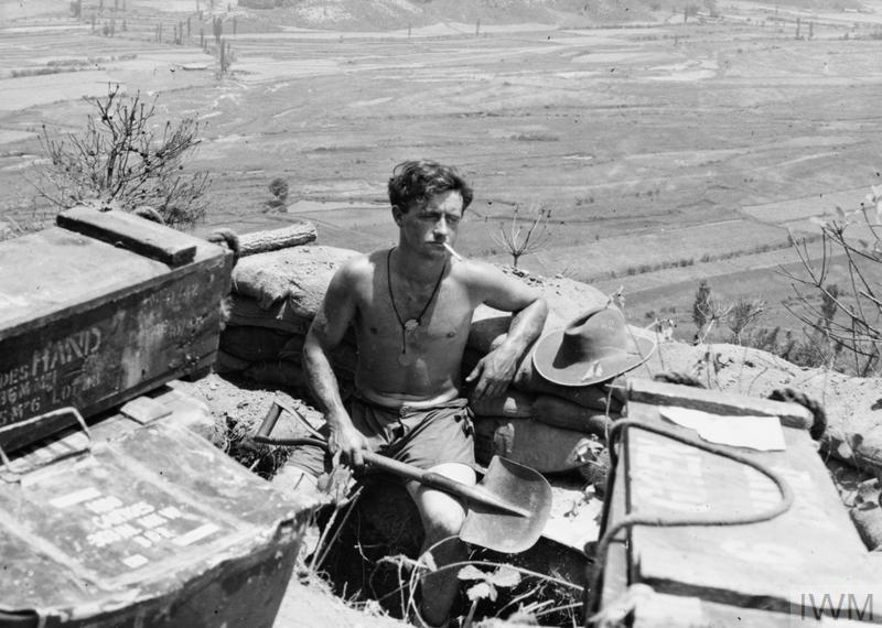 Private D J Dickson of the Royal Australian Regiment takes a rest after constructing a sandbag wall for his ammunition pit in Korea.