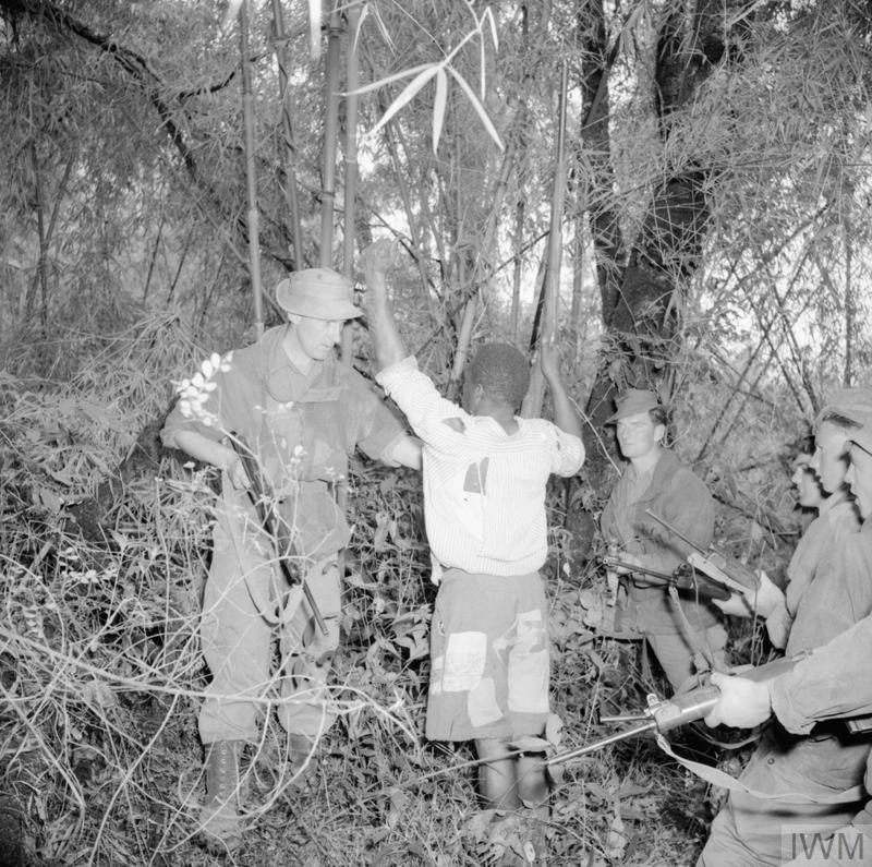 Members of a British Army patrol search a captured Mau Mau suspect.