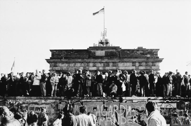 East and West Germans celebrate the lifting of travel restrictions on East Germans on a graffiti covered section of the Berlin Wall in front of the Brandenburg gate, November 1989.
