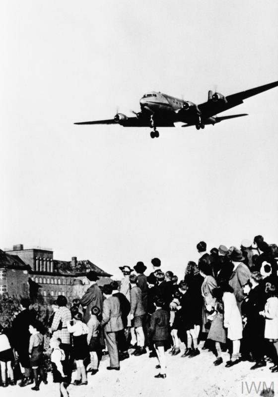 A Douglas C-54 Skymaster of the Military Air Transport Service, US Air Force coming in to land at Templehof Airport, Berlin, watched by a crowd of German civilians during the Berlin Airlift.