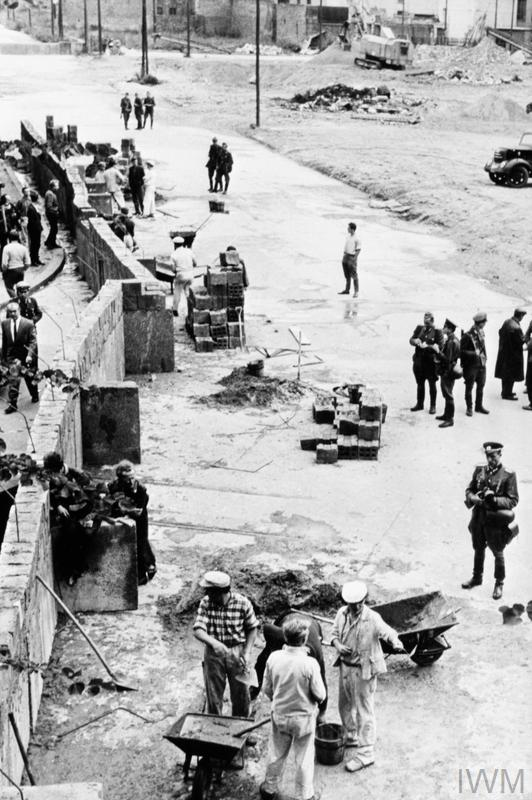 Construction workers, supervised by East German border guards, in the process of building the Berlin Wall.