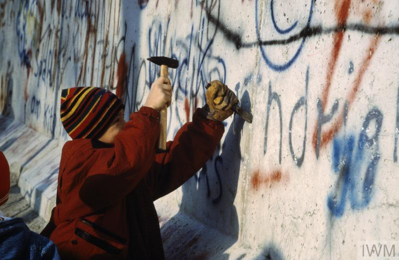 A child using a hammer and chisel to remove a piece of the Berlin Wall after its opening by the East German Government on 9 November 1989. By the end of 1990, much of the Wall had been demolished.