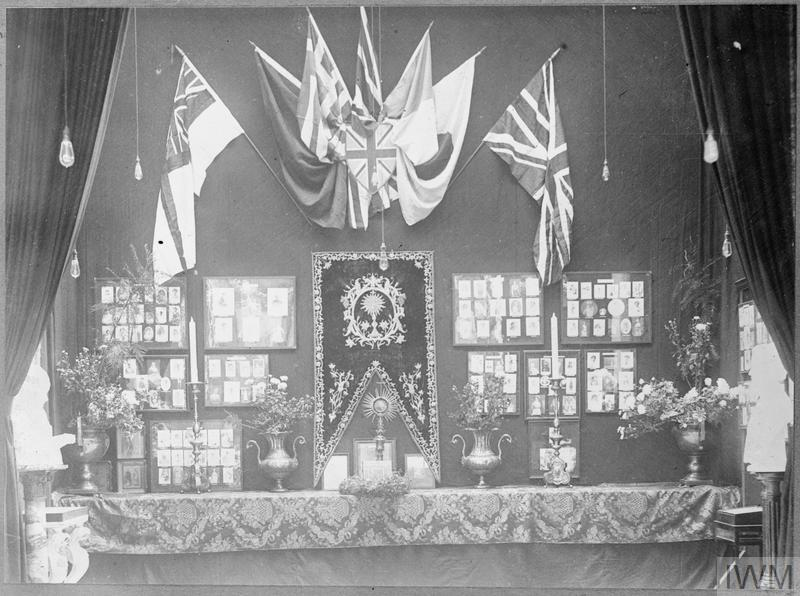 A general view of a Women's War Display at the Women's War Work Exhibition at Whitechapel. Photographs line the wall and flags and candles decorate the display.