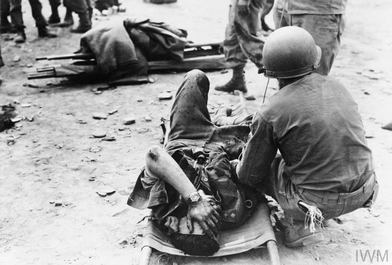 A wounded British lieutenant receives aid from 3rd US Division medics near Uijong-bu, Korea.