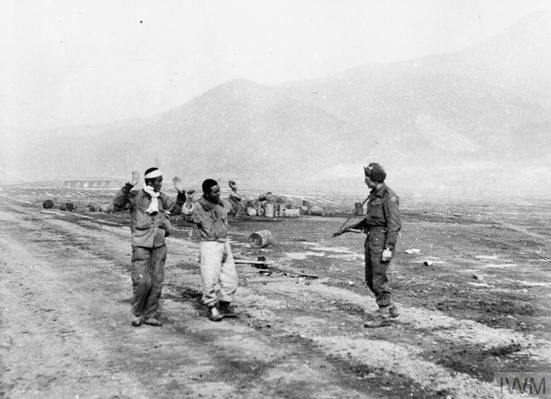 Private H Dawson of the 1st Battalion, The Gloucestershire Regiment, with two North Korean prisoners of war.