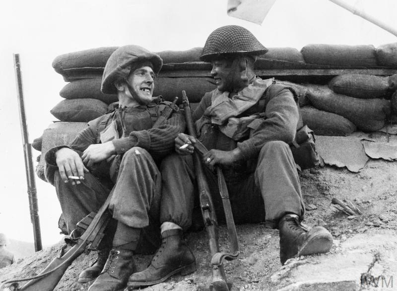 Two men of the 1st Battalion, The Black Watch rest and smoke before moving off on patrol after heavy fighting on the previous night. On the left, Private Jim McHale and on the right Corporal Kim Man Kyogh of South Korea, a KATCOM (Korean Augmentation to the 1st Commonwealth Division) soldier fighting alongside British troops.