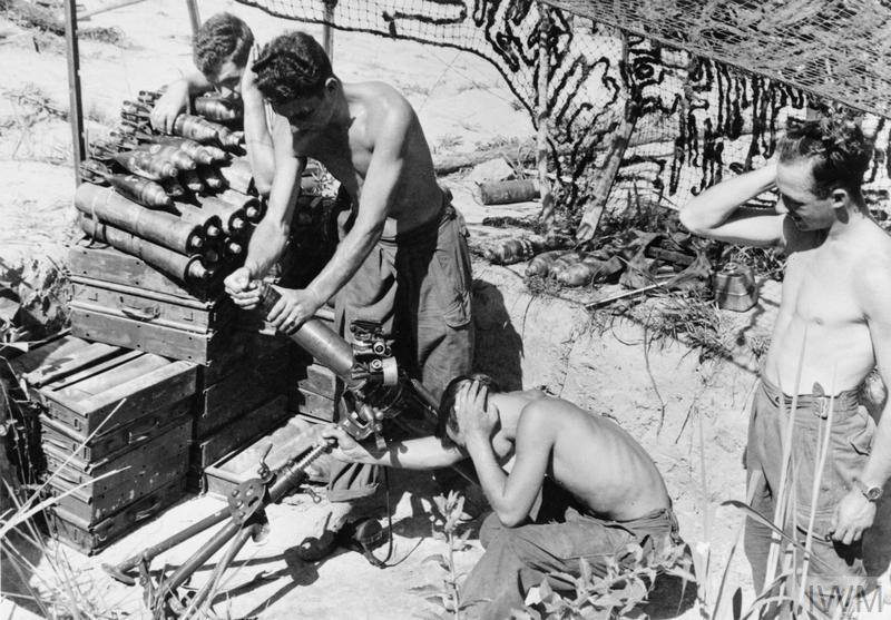 Stripped to the waist in a temperature of nearly 100 degrees Fahrenheit, men of a 3-inch mortar team of the 1st Battalion, The King's Own Scottish Borderers work overtime during an intensive bombardment of Chinese held hills. Left to right: Lance Corporal Bill Hunter; Private Jim Beveridge; and Private Tony Donaldson.