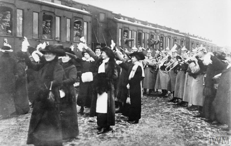 German reservists leaving Berlin for the front by train being waved off by civilians whilst a military band plays.