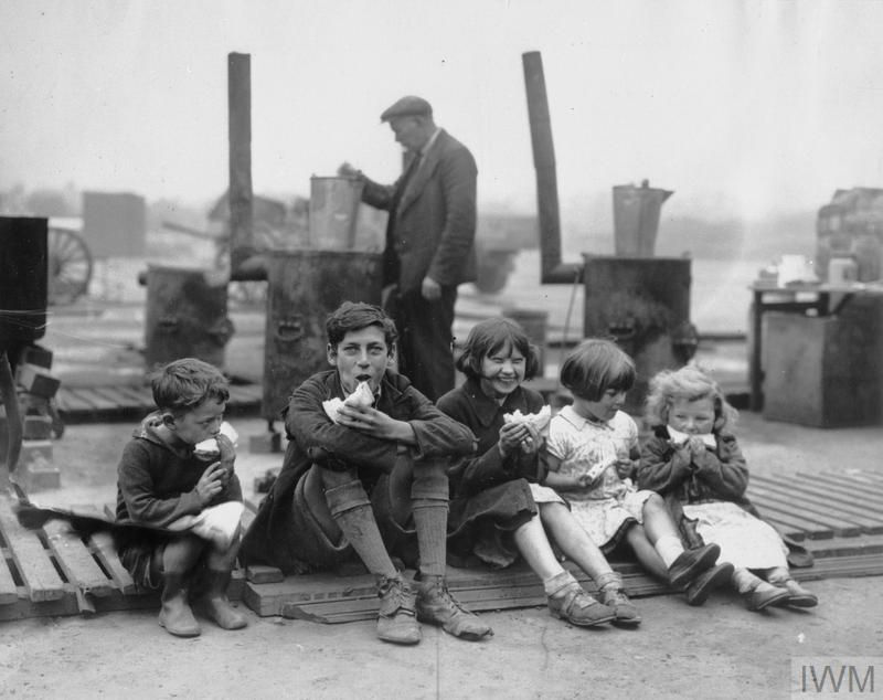 Five children eat American cheese sandwiches at an open-air emergency feeding centre in Liverpool. Behind them, a man can be seen cooking at one of several Soyer boilers or field cookers, available for use by civilians in the area.