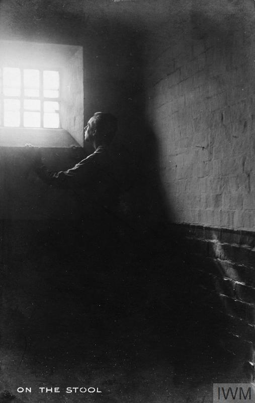 Copy negative made from a postcard of a conscientious objector prison. Original caption 'On the stool'.