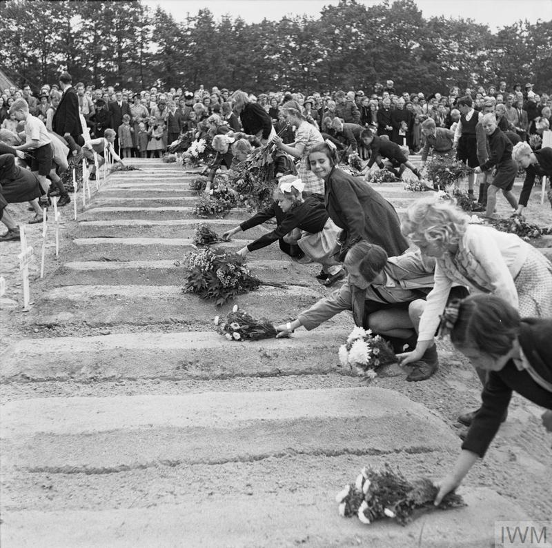 Dutch civilians and veterans watch as children place flowers on graves at the Arnhem-Oosterbeek Cemetery, 25 September 1945.