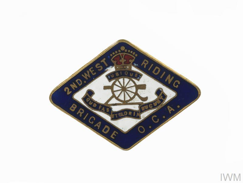 Enamel brooch pin badge with gold Royal Artillery symbol (with blue scrolls and red crown) in the white centre. Surrounded by a blue edge with inscription: 2ND. WEST RIDING BRIGADE O. C. A.