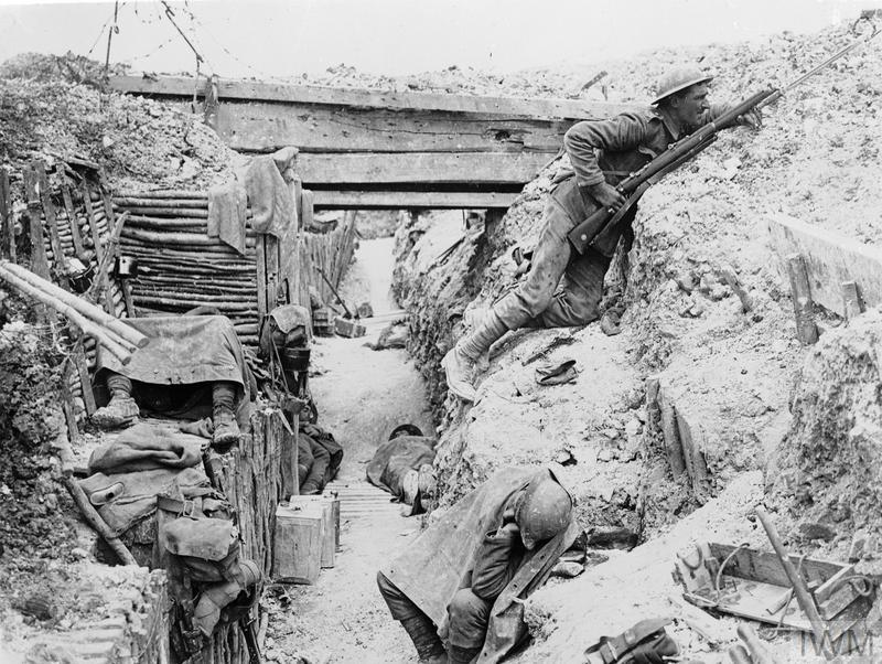 Soldiers of 'A' Company, 11th Battalion, the Cheshire Regiment, occupy a captured German trench at Ovillers-la-Boisselle on the Somme. In this photograph one man keeps sentry duty, looking over the parados and using an improvised fire step cut into the back slope of the trench, while his comrades rest.