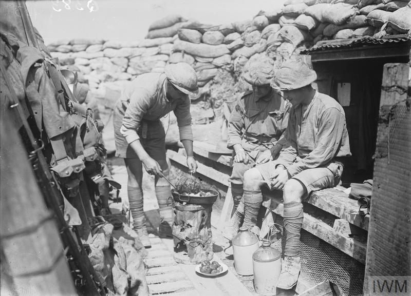 Men of the 2nd Australian Division in a front-line trench cooking a meal, Croix du Bac, near Armentieres. A variety of cooking methods were employed including primus stoves and braziers and soldiers produced a lunch of hot 'bully beef' hash from tins of corned beef.