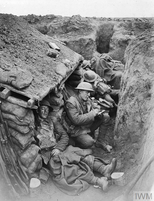 Four Canadian soldiers, sleeping and writing letters in the trenches near Willerval. Night time in the trenches was often a busy time; wiring parties, fatigue parties and raiding parties would all be sent out at night. The day time, therefore, was the time for relaxation and trying to catch a little sleep.