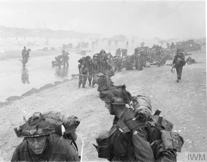 In the foreground are sappers of 84 Field Company Royal Engineers, part of No.5 Beach Group, identified by the white bands around their helmets. Behind them, medical orderlies of 8 Field Ambulance, RAMC, can be seen assisting wounded men. In the background commandos of 1st Special Service Brigade can be seen disembarking from their LCI(S) landing craft.