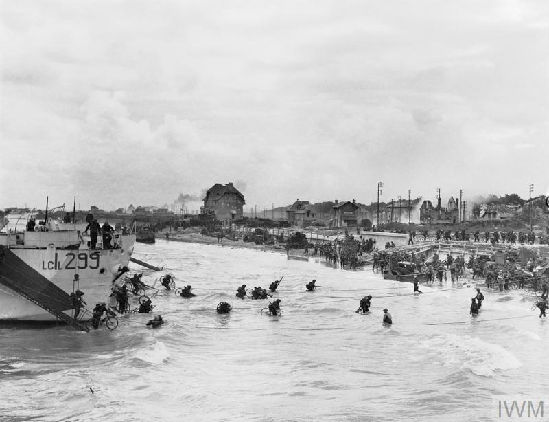 Troops of 9th Canadian Infantry Brigade disembarking with bicycles from LCI(L)s (Landing Craft Infantry Large) onto Nan White beach, Juno area, at Bernieres-sur-Mer, shortly before midday, 6 June 1944.