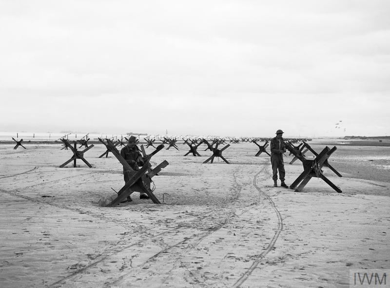 The British 2nd Army: Royal Navy Commandos at La Riviere preparing to demolish two of the many beach obstacles designed to hinder the advance of an invading army.
