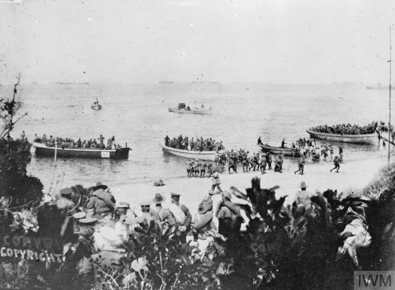 Australians landing at Anzac Cove at 8am, 25 April 1915 - part of the 4th Battalion and the mules for the 26th (Jacob's) Indian Mountain Battery. In the foreground is the staff of Colonel H N MacLaurin of the 1st Infantry Brigade. The officer with the rolled greatcoat over his shoulder is Major F D Irvine (killed on 27 April). Nearer the water's edge (centre) is Captain D M King, Orderly Officer. The officer on the left, with his chinstrap down, is Lieutenant R G Hamilton, the Brigade Signal Officer.