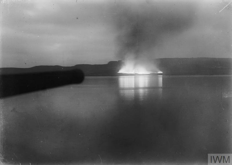 Distant view from the battleship HMS CORNWALLIS of stores burning on the beach after the evacuation of Suvla Bay, December 1915.