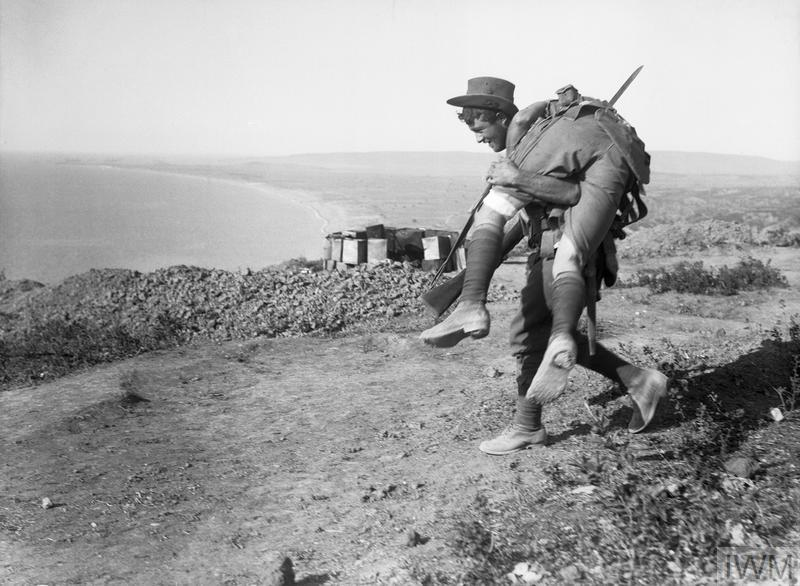 An Australian carrying a wounded comrade on his shoulders on Walkers Ridge down to a medical aid post. The men were cracking jokes as they made their way down from the front.