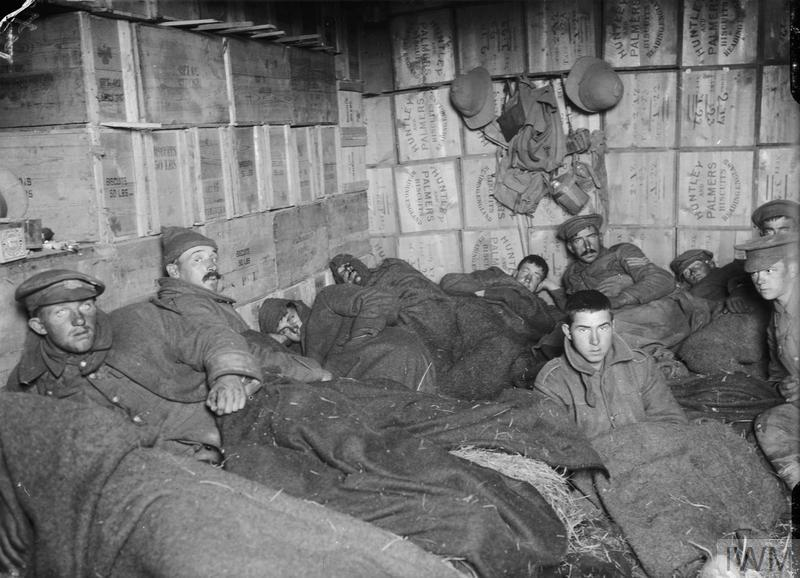 Frost-bitten soldiers lying on straw in shelters constructed of biscuit boxes at a store dump at Suvla, after the frost at the end of November 1915.