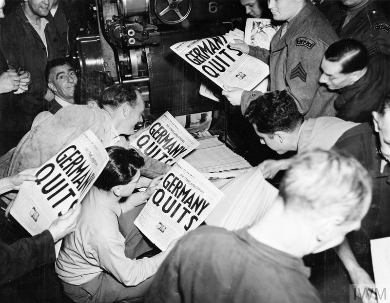 "Eager soldiers pulling copies of ""Stars and Stripes"" from the press of the London Times at 9 pm on 7 May 1945, when an extra edition was put out to announce the news of Germany's surrender. The headline reads ""Germany Quits""."