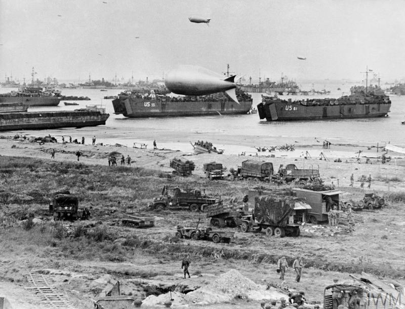 The scene on Omaha assault area after the initial landings on 6 June 1944, showing naval vessels massed offshore. In the foreground, LSTs (Landing Ship Tank), which have grounded on the beach, are unloading directly onto the shore.
