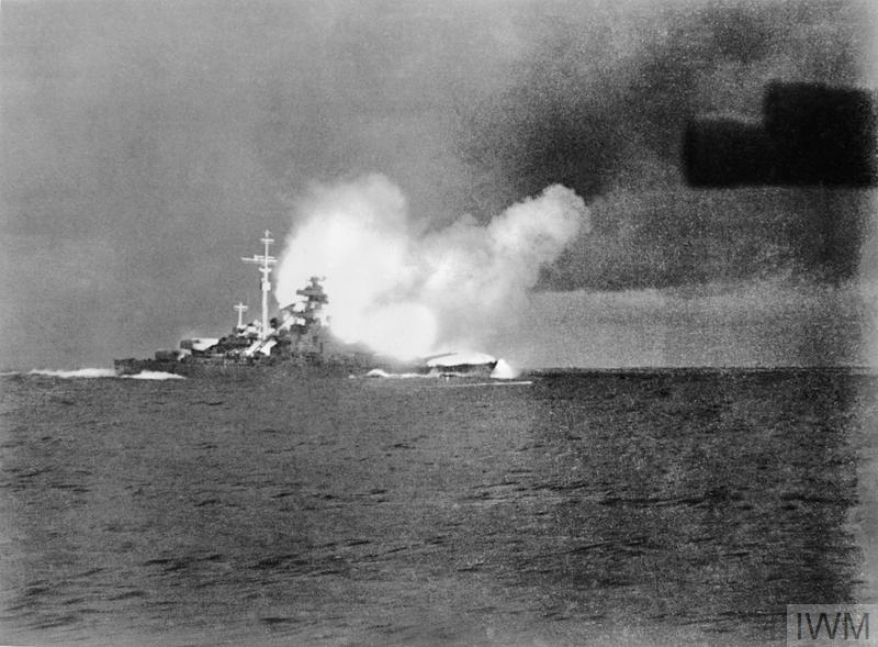 The German battleship BISMARCK firing at HMS HOOD during the action in the Denmark Strait. This photograph was taken from the German heavy cruiser PRINZ EUGEN.