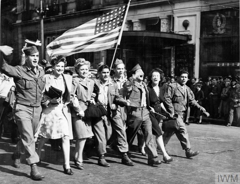 """On hearing on radio of the Japanese offer to surrender on 10 August 1945, American soldiers and English girls parade the """"Stars and Stripes"""" past the famous Criterion restaurant in Piccadilly Circus, London."""