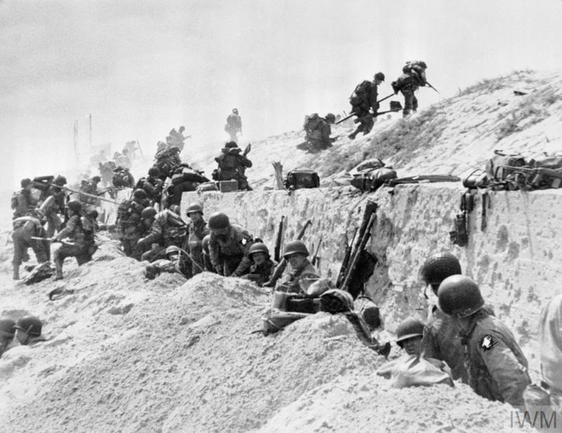 Troops of US VII Corps move over the sea wall on Uncle Red beach, Utah area, 6 June 1944.