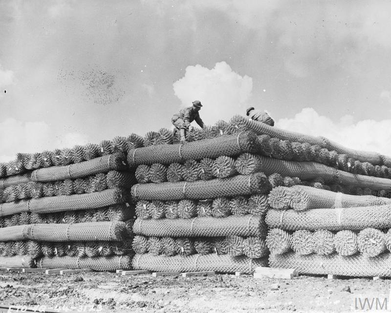 US soldiers pile great rolls of fence wire at a supply depot in England.