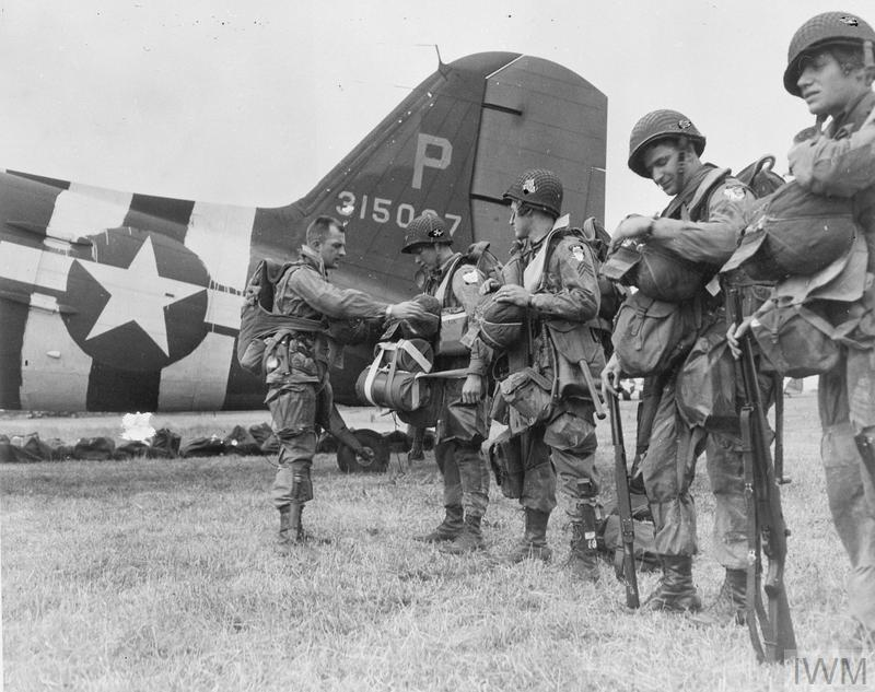 Airborne troops of 6th Airlanding Brigade admire the graffiti chalked on the side of their Horsa glider at an RAF airfield as they prepare to fly out to Normandy as part of 6th Airborne Division's second lift on the evening of 6 June 1944.