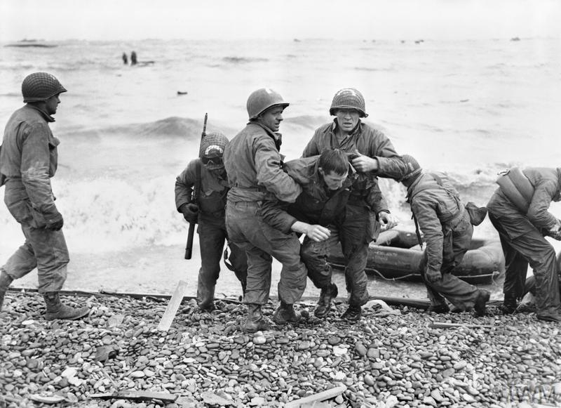 A survivor from a sunk American landing craft being helped ashore, Omaha assault area, 6 June 1944.