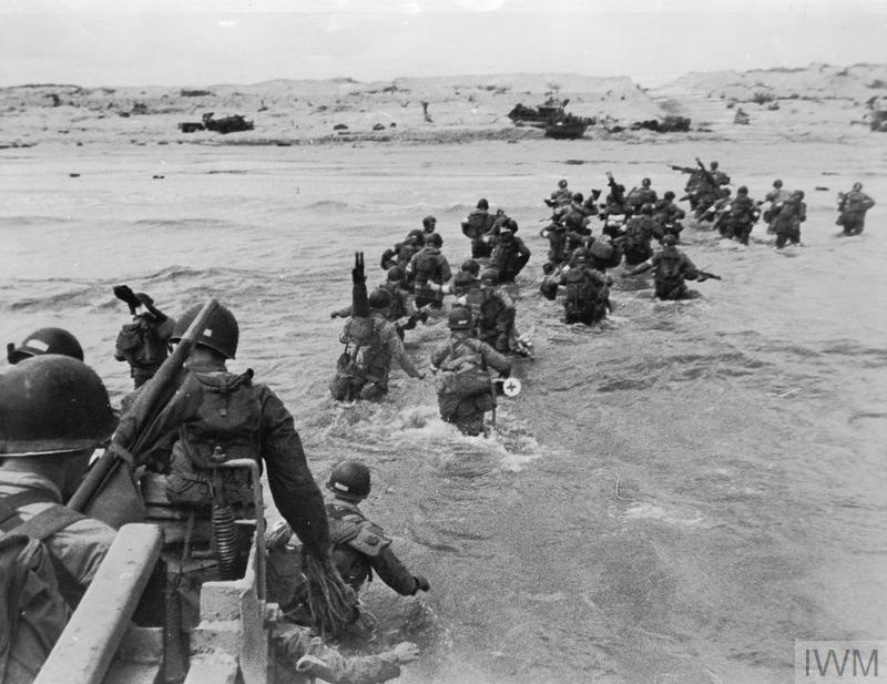 Troops of the US 7th Corps wading ashore on Utah Beach. Note the identifying bands worn on the left sleeve.