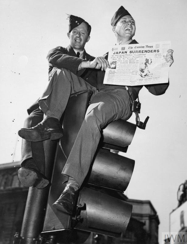 """Sergeant Franklin G Talley assisted by an RAF airman, holds up a copy of the Evening News while seated on traffic lights in Oxford Circus, London. The headline reads """"Japan Surrenders""""."""